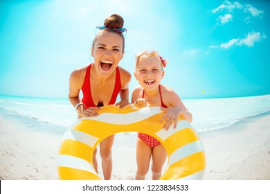 happy young mother and daughter in red swimwear on the seacoast holding yellow inflatable lifebuoy