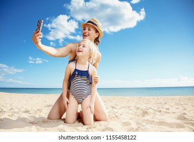 happy young mother and daughter in swimsuit taking selfie with mobile phone on the beach