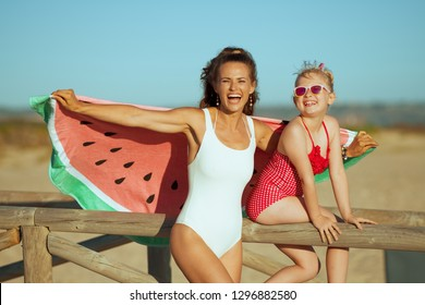 happy young mother and daughter in swimsuit on the seashore in the evening having fun time holding funny watermelon towel. mother and daughter near a wooden fence. carefree beach fun.