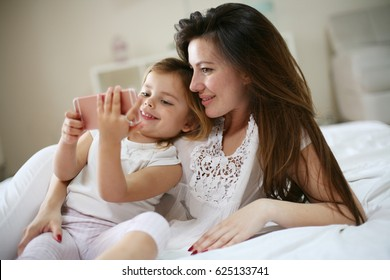 Happy young mother with daughter using smart phone on bed at home.