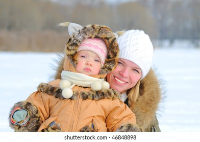 Happy young mother and daugther in winter clothing hugging