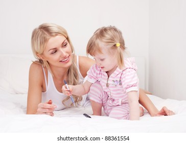 happy young mother drawing with her daughter on the bed at home (focus on the woman)