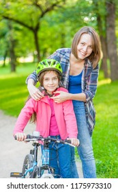 Happy young mother dresses her daughter's helmet