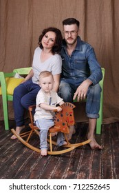 Happy young mother, father sit on bench and little son poses on rocking horse in studio