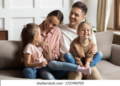 Happy young mother and father with two little daughters sitting on couch, looking at each other, family enjoying tender moment, smiling parents and preschool children having fun together