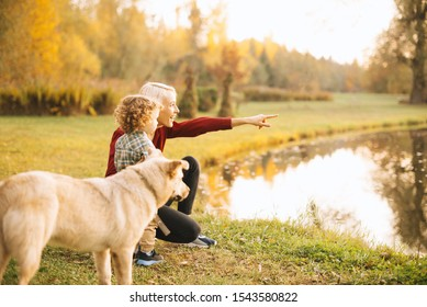 Happy young mother having beautiful time with her kid outdoor in nature and having walk with dog