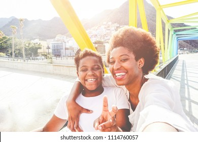 Happy young mother having fun with her child in summer sunny day - Son taking selfie with his mum outdoor - Family lifestyle, motherhood, love and technology concept - Main focus on woman face