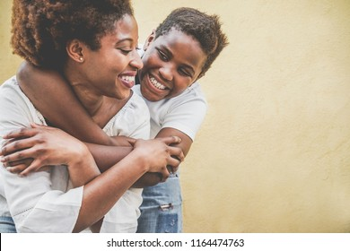 Happy young mother having fun with her child - Son hugging his mum outdoor - Family lifestyle, motherhood, love and tender moments concept - Focus on kid face