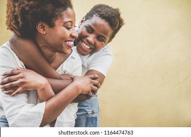 Fröhliche junge Mutter, die Spaß mit ihrem Kind hat - Son umarmt seine Mutter im Freien - Familienleben, Mutterschaft, Liebe und zarte Momente Konzept - Fokus auf das Gesicht des Kindes