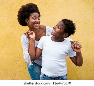 Happy young mother having fun with her child - Mom playing and dancing with his son - Family lifestyle, motherhood, love and tender moments concept - Focus on mum face