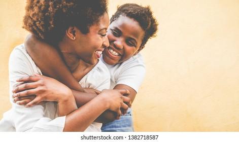 Fröhliche junge Mutter, die Spaß mit ihrem Kind hat - Son umarmt seine Mutter im Freien - Familienverbindung, Mutterschaft, Liebe und zarte Momente Konzept - Fokus auf das Auge der Frau