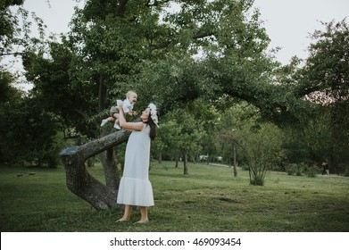 Happy young mother having fun, bowl, rising up, piggyback ride her child in park on summer sunset