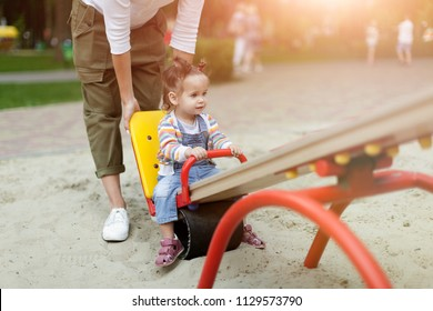 Happy young mother with her baby girl playing in colorful playground for kids. Mom with toddler having fun at summer park. Baby play. Summer family leisure.