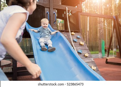 Happy young mother with her baby boy playing in colorful playground for kids. Mom with toddler having fun at summer park. Baby play in children's slide