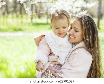 Happy young mother with her baby daughter outdoors in a spring park.
