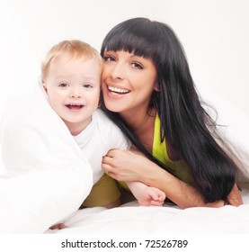 happy young mother and her baby on the bed at home (focus on the mother)