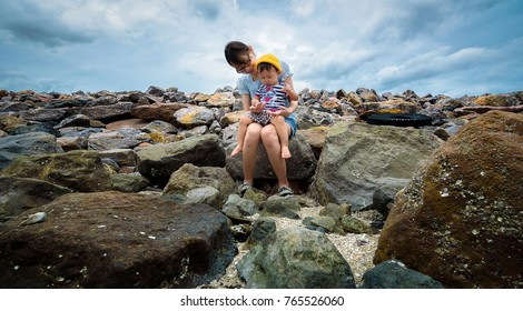 Happy young mother with her baby sit on stones and enjoy beautiful summer day