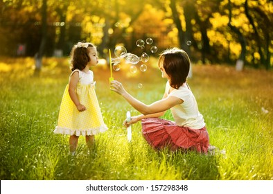 Happy young mother and her daughter blowing soap bubbles in autumn