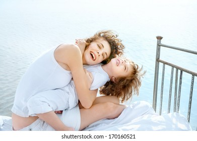 Happy young mother and her kid embrace on vintage bed against sea
