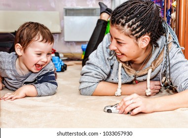 Happy young mother and her little son play in the toys in the living room at home. Happy family spending time together at home.
