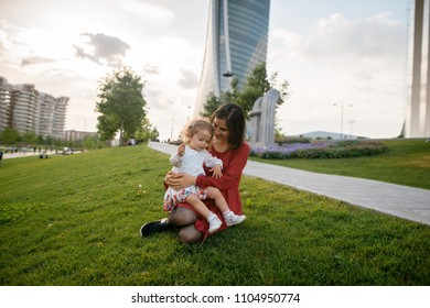 Happy young mother and her little daughter sitting on the green lawn in the park. Family day. Skycraper background