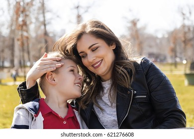 happy young mother and her nine year old son in the summer park.