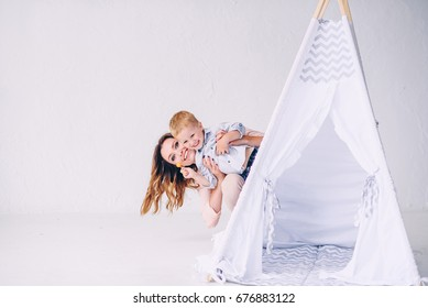 Happy young mother with her smiling son looks out of a child's wigwam in the light room.