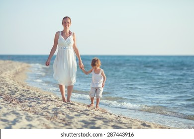 Happy young mother and her son walking by the sea