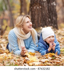 happy young mother and her son spending time in the autumn park