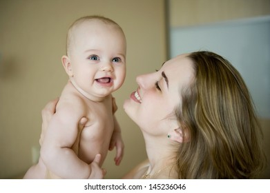 Happy young mother holding her newborn baby boy skin to skin and playing with him