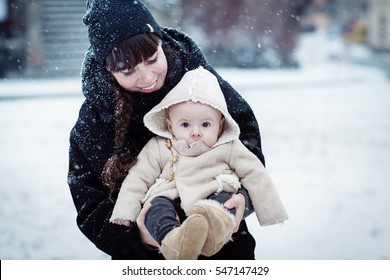 Happy young mother holding her newborn baby in the cute sheep coat with hood. Mother and new born boy having good time in the park in winter. Baby boy is looking on the camera. Color toned image.