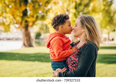 Happy young mother holding sweet toddler boy, family having fun together outside on a nice sunny day