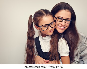Happy young mother and kid girl in fashion glasses hugging on empty copy space background.  Toned closeup portrait