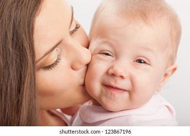 happy young mother  kissing baby girl