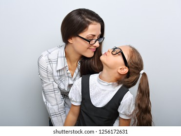 Happy young mother and lauging kid in fashion glasses hugging and looking each other on empty copy space background