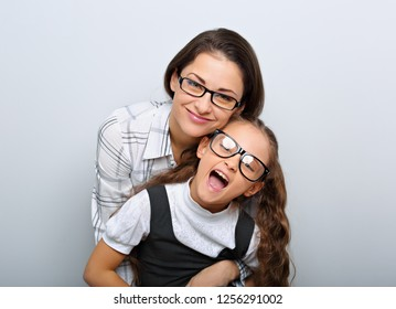 Happy young mother and lauging kid in fashion glasses hugging on empty copy space background