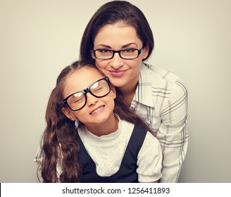 Happy young mother and lauging kid in fashion glasses hugging on empty copy space background. Family closeup portrait. Toned color