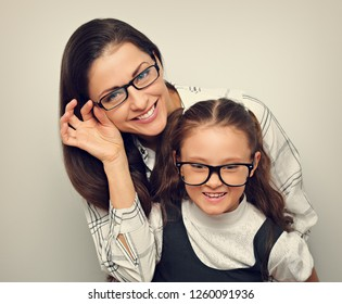 Happy young mother and lauging kid in fashion glasses hugging on empty copy space background. Vintage portrait