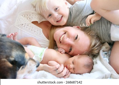 Happy Young Mother Laying in Bed with Toddler Son and Newborn Baby Daughter