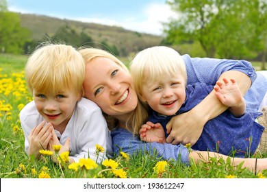 a happy young mother is laying outside hugging her two young children in a field of Dandelion flowers on a Spring day.
