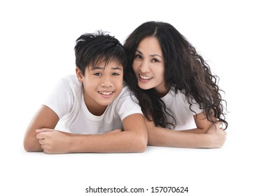 Happy young mother lying on the wooden floor with her son