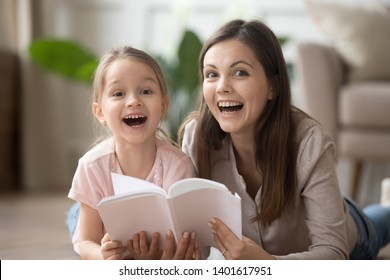 Happy young mother or nanny and funny little girl child lying on warm floor reading book together, smiling mom and preschooler daughter have fun flipping textbook look at camera laughing