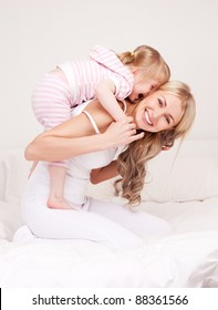 happy young mother playing with her daughter on the bed at home