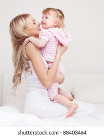 happy young mother playing with her daughter on the bed at home (focus on the woman)