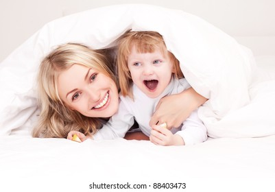 happy young mother playing with her daughter under the blanket on the bed at home (focus on the woman)