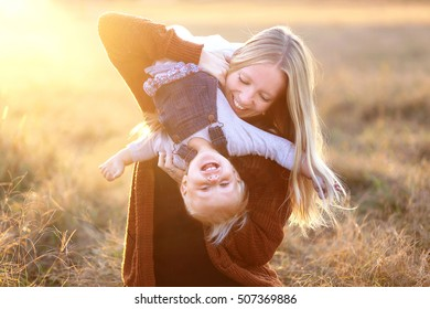A happy young mother is playing outside with her one and a half year old baby daughter, holding her upside-down and laughing at sunset.