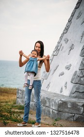 Happy young mother playing with a small daughter, throwing in the air, outdoors background