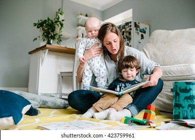 Happy young mother reading a book to their children sitting in the floor of the house. The concept of family