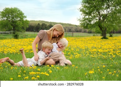 A happy young mother is sitting in in a meadow of dandelion flowers with her two children, laughing, tickling, and playing.