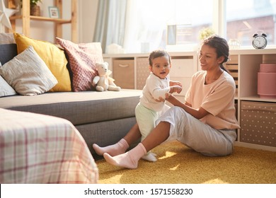 Happy young mother sitting on the floor smiling and playing with her child in the living room
